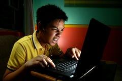 Adolescente asiático, intenso jugando o trabajando en un ordenador portátil Imagen de archivo