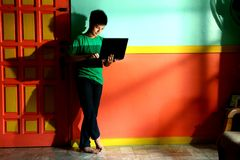 Adolescente asiático joven con un ordenador portátil en una sala de estar Imágenes de archivo libres de regalías