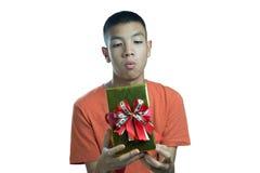 Adolescente asiático joven que se pregunta qué en la caja Foto de archivo libre de regalías