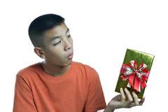 Adolescente asiático joven que se pregunta qué en la caja Imagenes de archivo