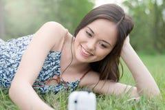Adolescente asiático joven que usa smartphone Fotos de archivo