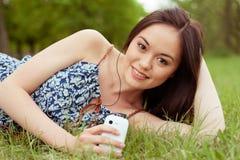Adolescente asiático joven que usa smartphone Fotos de archivo libres de regalías