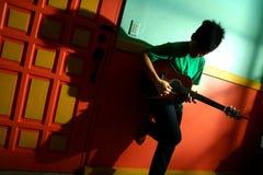 Adolescente asiático joven tocando la guitarra en una sala de estar Imagenes de archivo
