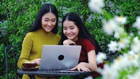 Adolescente asiático lindo con el ordenador portátil en el jardín en la casa Imagenes de archivo