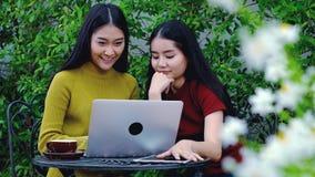 Adolescente asiático lindo con el ordenador portátil en el jardín en la casa Imagen de archivo libre de regalías