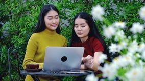 Adolescente asiático lindo con el ordenador portátil en el jardín en la casa Fotografía de archivo libre de regalías