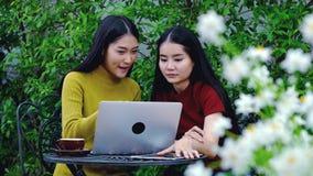 Adolescente asiático lindo con el ordenador portátil en el jardín en la casa Fotos de archivo libres de regalías
