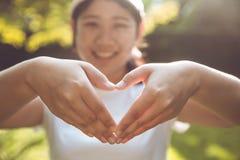 Adolescente asiático lindo con la muestra del amor de la mano Fotos de archivo