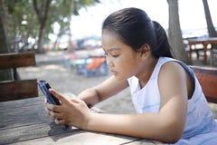 Adolescente asiático a mirar el teléfono móvil Imagen de archivo