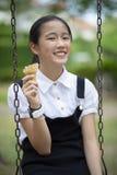 Adolescente asiático que come o cone de gelado com a cara da felicidade no verde Imagens de Stock