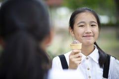 Adolescente asiático que come o gelado com cara da felicidade Fotos de Stock Royalty Free