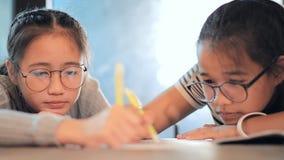 Adolescente asiático que escreve algo na tabela da escola video estoque