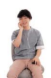 Adolescente asiático que escucha la música Imagen de archivo libre de regalías