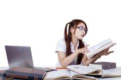 Adolescente asiático que estudia en la tabla Imagen de archivo libre de regalías