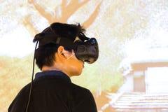 Adolescente asiático que experimenta el gad del entretenimiento de la realidad virtual de VR Imagen de archivo libre de regalías