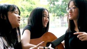 Adolescente asiático que joga a guitarra e que canta a música vídeos de arquivo
