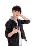 Adolescente asiático que mira su teléfono móvil Foto de archivo