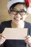 Adolescente asiático que muestra al tablero de madera en blanco Imagenes de archivo