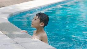 Adolescente asiático que nada al aire libre en piscina azul en verano Imagen de archivo libre de regalías