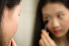 Adolescente asiático que pone en maquillaje Fotos de archivo
