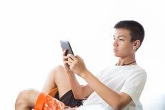 Adolescente asiático que reclina y que usa su tableta Fotografía de archivo libre de regalías