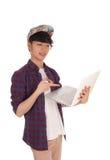Adolescente asiático que señala en su ordenador portátil Fotografía de archivo libre de regalías