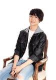 Adolescente asiático que se sienta en butaca vieja Fotografía de archivo libre de regalías