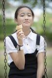 Adolescente asiático que se sienta en el oscilación y que come happine del helado del cono Imágenes de archivo libres de regalías