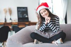 Adolescente asiático que se sienta a piernas cruzadas en el sofá con la Navidad h Imagen de archivo