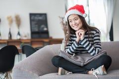 Adolescente asiático que se sienta a piernas cruzadas en el sofá con el sombrero a de santa Fotos de archivo