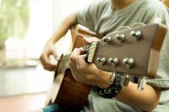 Adolescente asiático que toca la guitarra acústica Imagen de archivo libre de regalías