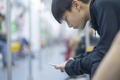Adolescente asiático que usa el teléfono elegante en el MRT Fotografía de archivo libre de regalías