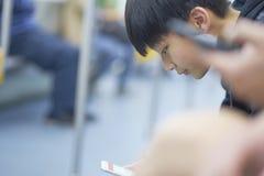 Adolescente asiático que usa el teléfono elegante en el MRT Imagenes de archivo
