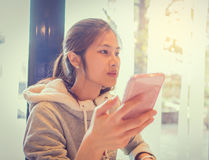 Adolescente asiático que usa el teléfono móvil Fotos de archivo