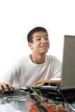 Adolescente asiático que usa o computador com cara smily Foto de Stock