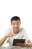 Adolescente asiático que usa su tableta con sonrisa Fotografía de archivo libre de regalías