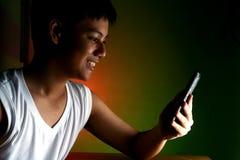 Adolescente asiático que usa un smartphone o un teléfono móvil Imágenes de archivo libres de regalías