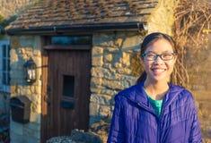 Adolescente asiático sonriente feliz delante de la casa de piedra vieja de Cotw Imágenes de archivo libres de regalías