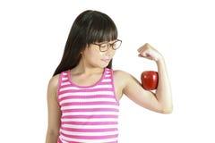 Adolescente asiático sonriente que muestra los músculos con la manzana roja Fotografía de archivo libre de regalías