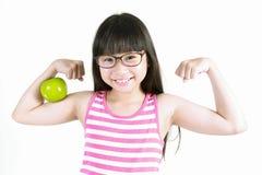 Adolescente asiático sonriente que muestra los músculos con la manzana roja Fotos de archivo libres de regalías