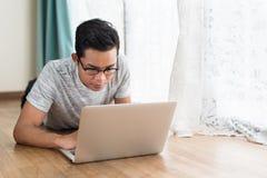 Adolescente asiático usando el ordenador portátil mientras que miente en un piso Fotos de archivo libres de regalías
