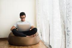 Adolescente asiático usando el ordenador portátil mientras que se relaja Imagen de archivo
