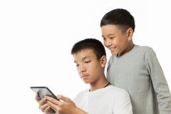 Adolescente asiático y su hermano que comparten la buena información con el SMI Foto de archivo