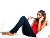 Adolescente asiatico arrabbiato sul sofà e sul telefono Fotografia Stock