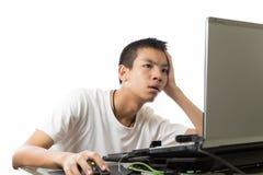 Adolescente asiatico che per mezzo del computer con il fronte noioso Fotografia Stock
