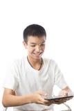 Adolescente asiatico che per mezzo della sua compressa con il sorriso Fotografia Stock