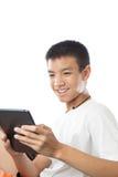 Adolescente asiatico che per mezzo della sua compressa con il sorriso Fotografia Stock Libera da Diritti