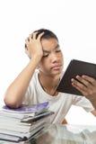 Adolescente asiatico che per mezzo della sua compressa e ritenendo annoiato sopra la t Fotografia Stock