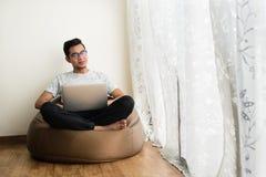 Adolescente asiatico facendo uso del computer portatile mentre rilassandosi immagine stock libera da diritti