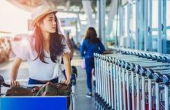 Adolescente asiatique de femme avec la marche de chariot de bagages photos stock